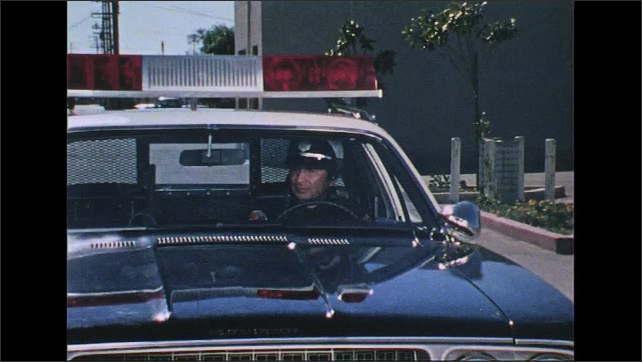 UNITED STATES 1970s: Police car drives toward camera, stops, zoom in on officer / Car drives down street turns corner / Police car enters street, follows car.