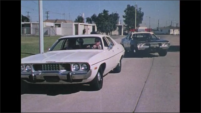 UNITED STATES 1970s: Car stops on street, police car pulls up behind / Officer exits car with gun.