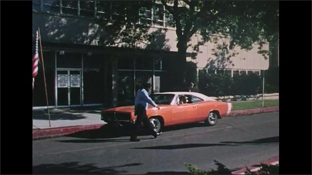 UNITED STATES 1970s: Car outside of police station, officers exit, zoom in, officer gets into car / Car drives away from camera.