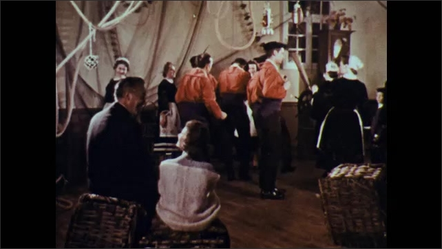 1960s: Man playing bagpipes with man playing horn. People dancing in costume, man and woman sitting in foreground. High angle view of dancers.