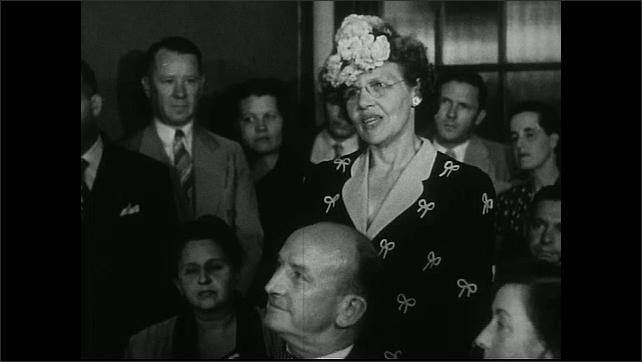 United States 1950s. Woman with floral hat stands up to speak at a meeting.