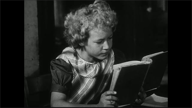 United States 1950s. Boy in ripped t-shirt sits down in class. Girl with messy hair reads worn out book. Boy reads old book.