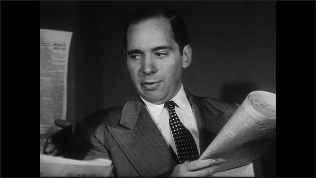 United States 1950s.  People walk through town. Men with newspaper speak.