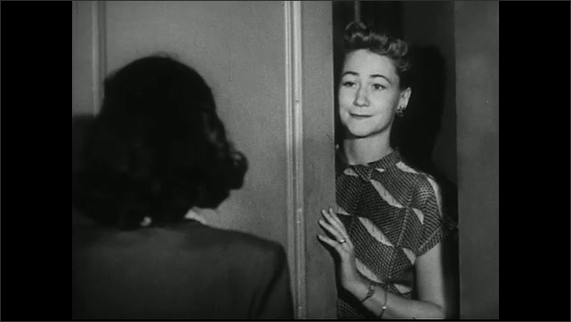 United States 1950s. Woman speaks to another woman at her front door. Woman shuts door. People and cars outside polling place.