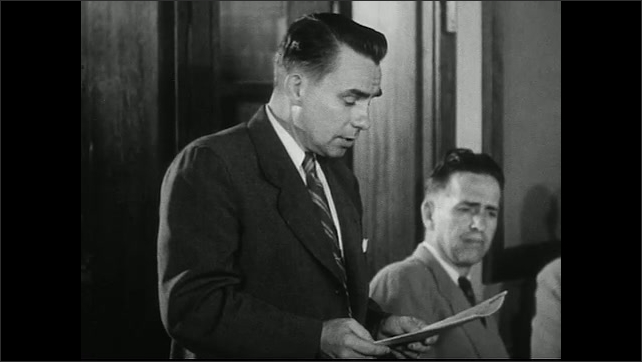 """United States 1950s. Sign says """"Advisory Committee Meeting."""" People at meeting. Man speaks."""