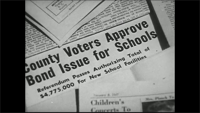 United States 1950s. Man speaks at meeting. Newspaper headline about school board. Man and woman point at building.
