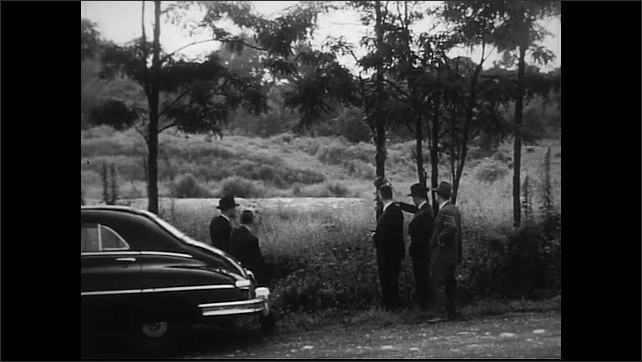 United States 1950s. Man and woman point at building. Men gather around car point at field.