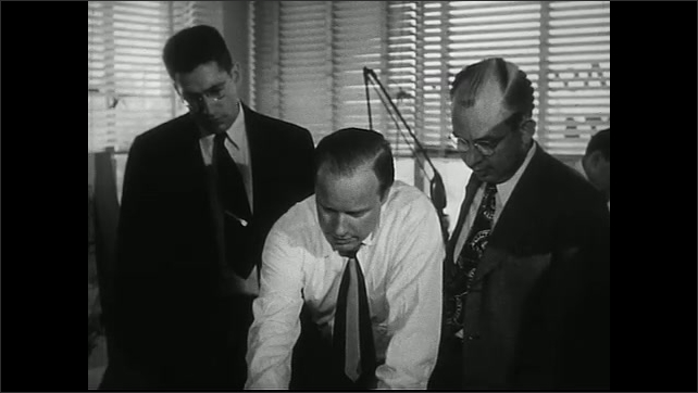 United States 1950s. Male architects discuss drawing.
