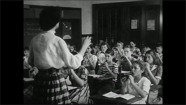 United States 1950s. Doctor examines child's throat. Female music teacher instructs class as they play recorders.