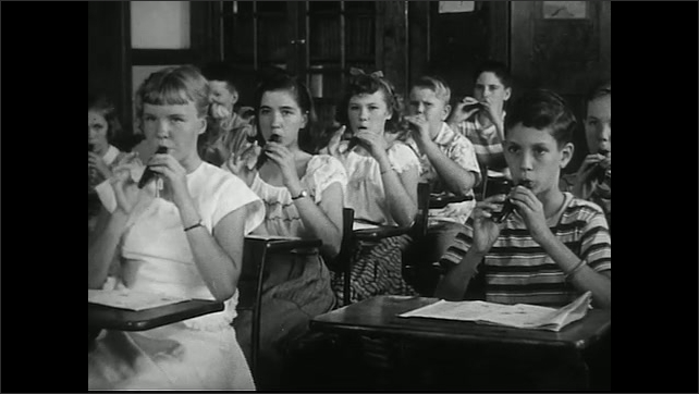 United States 1950s. Female music teacher instructs class as they play recorders.