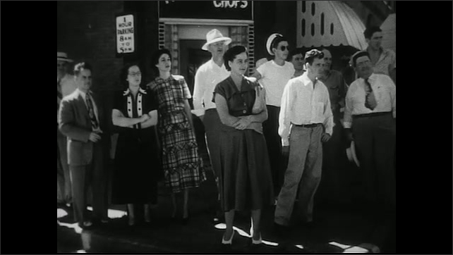 United States 1950s. Group of people stand on sidewalk.
