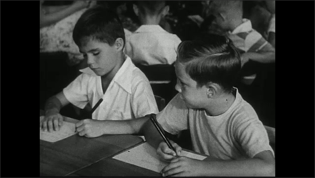 United States 1950s. Teacher in classroom with students drawing, writing, and reading.