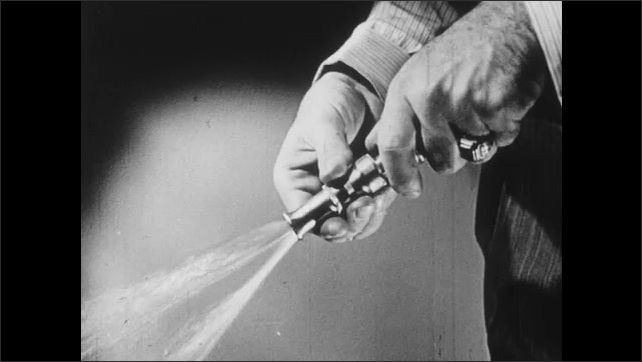 1940s: UNITED STATES: hand holds garden hose. Adjustable nozzle on garden hose. Hand turns off garden hose tap