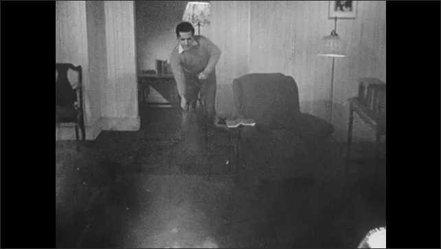 1940s: UNITED STATES: man sprays foam on fire bomb in home. Man pumps water from tank.
