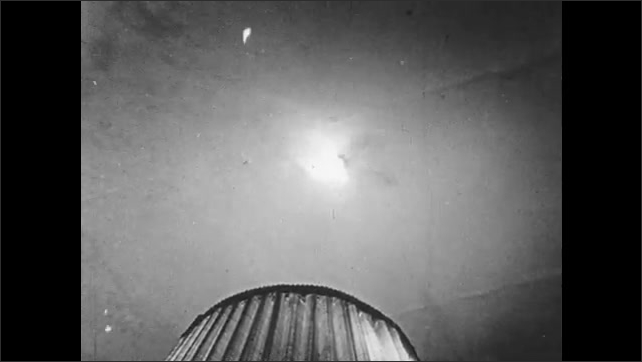 1940s: UNITED STATES: close up of fire bomb and sparks. Ceiling affected by fire bomb. Attic paper roll. Man rolls out paper on ground