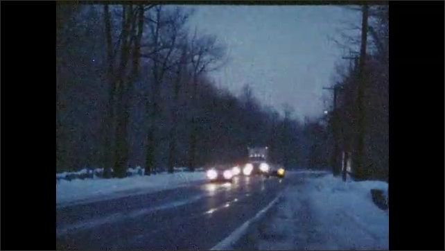 1980s: UNITED STATES: man and lady at site of minor accident. Cars drive along road at night. Man and woman in car at night