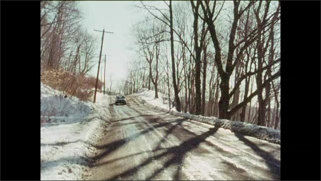 1980s: UNITED STATES: man drives car in winter. Man holds map in hand. Car drives along icy road. Snow by road. Dirty windshield. Wipers clean windscreen