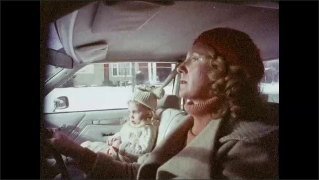1980s: UNITED STATES: car drives along road in snow. Lady drives home with children. Girl sat in car. Lady forgets to put on seatbelt. Child plays with hat