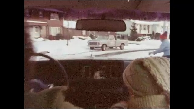 1980s: UNITED STATES: Watch Children sign. Children play in car. Child rides bike in front of car. Bike in snow. Lady slams on brakes