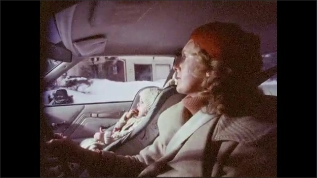 1980s: UNITED STATES: lady drives car in winter. Car drives along road. Lady wears seatbelt in car. Children wear seatbelts. Children occupied with activities in back of car