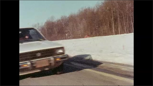 1980s: UNITED STATES: man sees exit sign. Exit sign by road. Cars collide on road. Car causes accident. Snow by road. Car pulls over