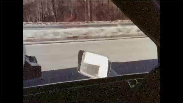 1980s: UNITED STATES: man holds map and steering wheel. Car lights at night. Wipers on dirty window. Man looks through window of car. Cars on road