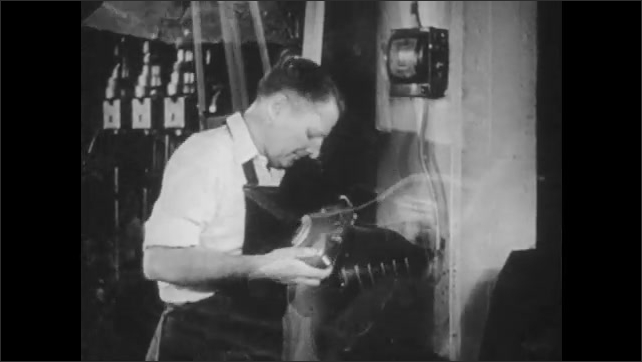 1940s: UNITED STATES: men work in shoe factory. Man grinds down shoe on machine. Cobbler at work. Client pays cobbler