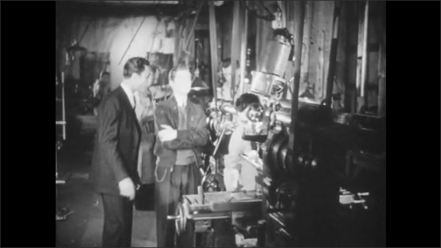 1940s: UNITED STATES: boy visits work place. Man shows young man around work place. Students watch movie.