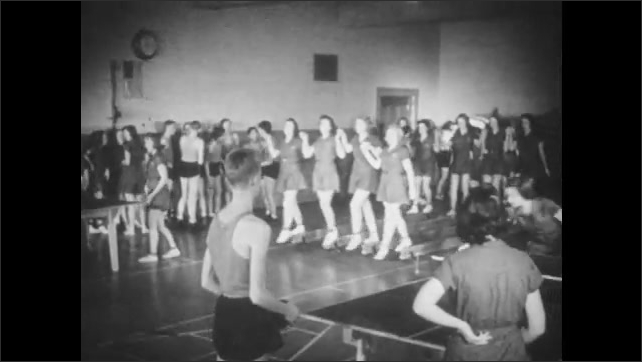1940s: UNITED STATES: Gymnasium title. Students take part in physical exercise in gym