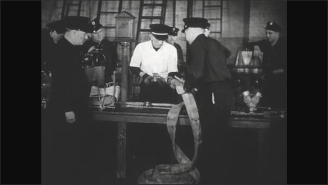UNITED STATES 1940s :  Fire captain shows his class how to properly place a nozzle on a fire hose.