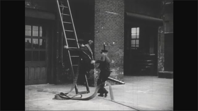 UNITED STATES 1940s :  Firefighters practicing pulling a fire hose from the fire truck and bringing it to the top of a building.
