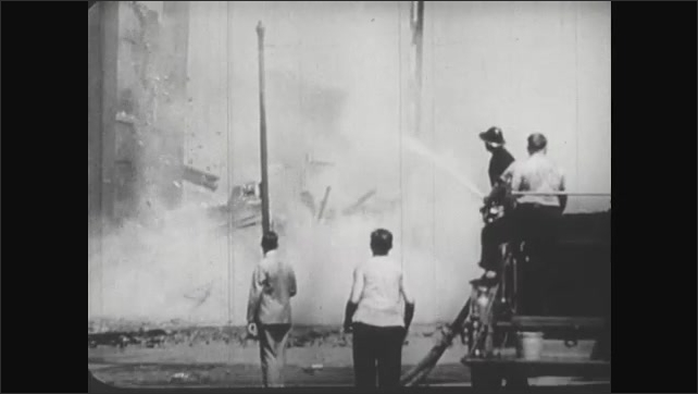 UNITED STATES 1940s :  As firefighters attempt to put out the flames in a building, it crumbles.