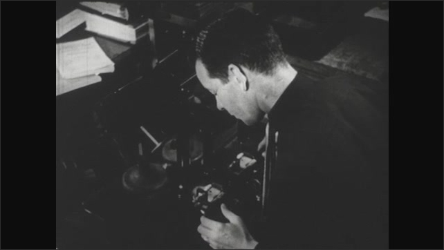UNITED STATES 1940s :  A man operates machinery as a scientist looks through a microscope.
