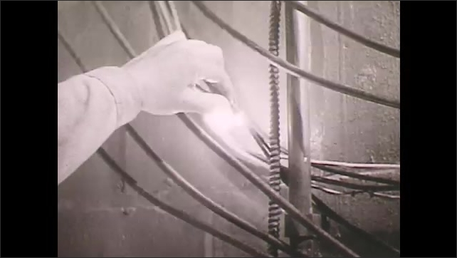 1950s: Improperly supported wires in boiler room.  Man pushes wires together and creates spark.  Electrical fuses.  Man opens fuse box.