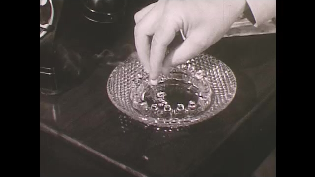 1950s: Hand puts out cigarette in ashtray.  Full garbage can.  Smoke appears in trash.