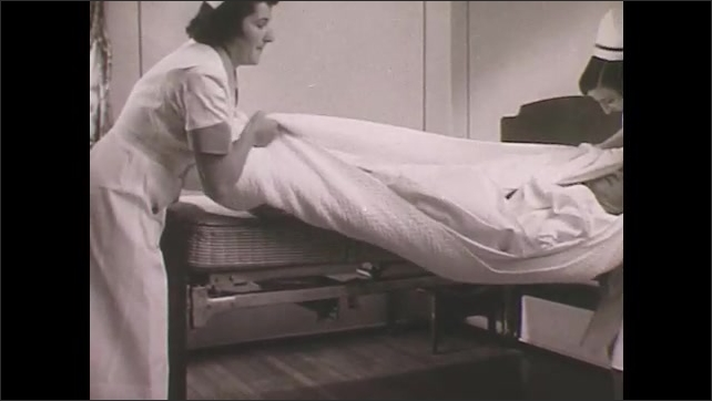 1950s: Nurse walks with amputee on crutches.  Nurses and orderlies push patients in wheelchairs and on gurneys.  Nurses use bedding to lift and drag patient down hallway.  Woman closes door.