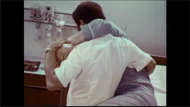 1970s: Male nurse removes patient's sheets and lifts him from bed. Nurse moves patient from room using a hip carry technique.