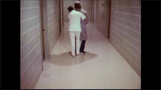 1970s: Patient in robe wanders hospital hallway. Nurse approaches patient from behind and embraces them. Nurse holds patient and guides them down hallway.