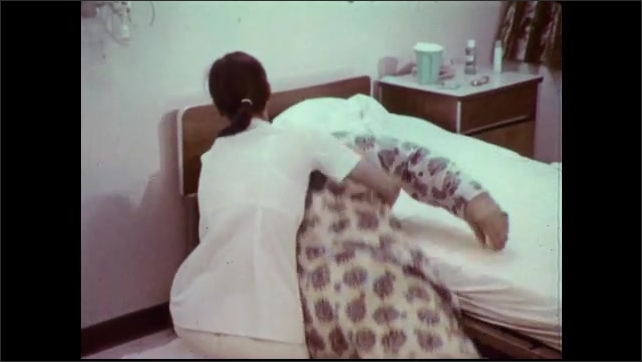 1970s: Nurse adjusts large patient in hospital bed. Nurse kneels near bed and drags patient onto blanket on floor. Nurse drags patient from room.