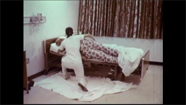 1970s: Nurse lies blanket next to hospital bed. Nurse slides obese patient from bed onto floor. Nurse drags patient out of the room.