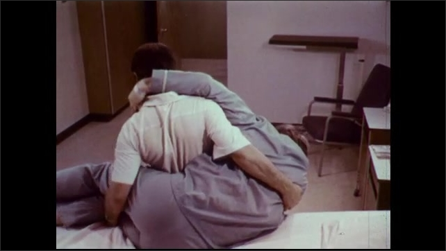 1970s: Male nurse lifts patient from bed in the hip carry position. Nurse carries man from room.