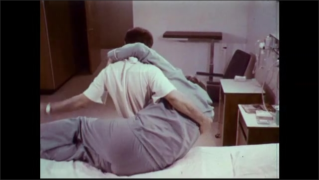 1970s: Man lies in hospital bed. Male nurse lifts patient from bed in the hip carry position. Nurse carries man from room.