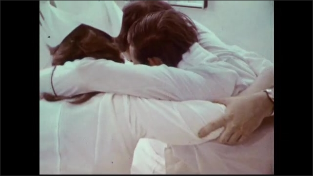 1970s: Nurses adjust patient in bed. Nurses wrap arms around patient and lift him using the swing carry. Nurses carry patient from hospital room.