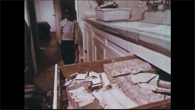1960s: Girl searches for jacks under the bed with flashlight. Girl puts matchbooks and open box of matches into a metal coffee can.