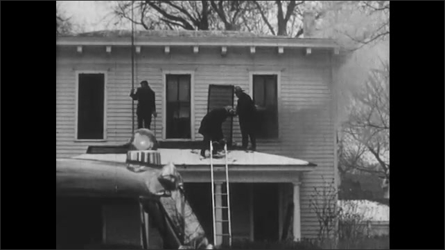 1950s: UNITED STATES: boy speaks on telephone by wall. Firemen stand on porch roof. Men put out fire in home.  Girl cooks in kitchen