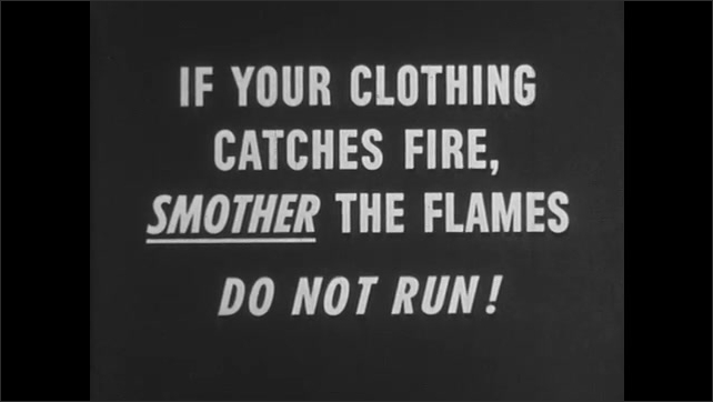 1950s: UNITED STATES: girl's clothes catch fire. Girl rolls on floor in rug. Teacher leads lesson in classroom. Boy stands by black board. Students sit at desks in classroom