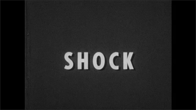 1950s: Men stand in construction site, talk. Man runs over to man on ground, check's man over, lays man down. Title card, shock. Men rotate man's body on ground.