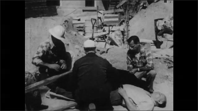 1950s: Man lifts up man's feet, man places rocks under feet. Man runs over with blanket, men wrap blanket around man on ground.