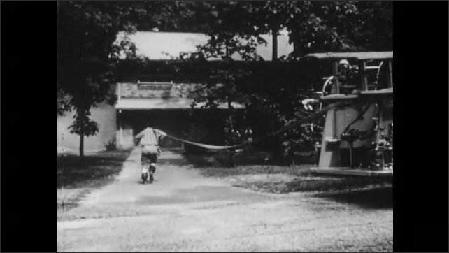 1950s: Fire truck drives down street, stops in front of house, man jumps off truck, drags hose to house. People evacuate house.