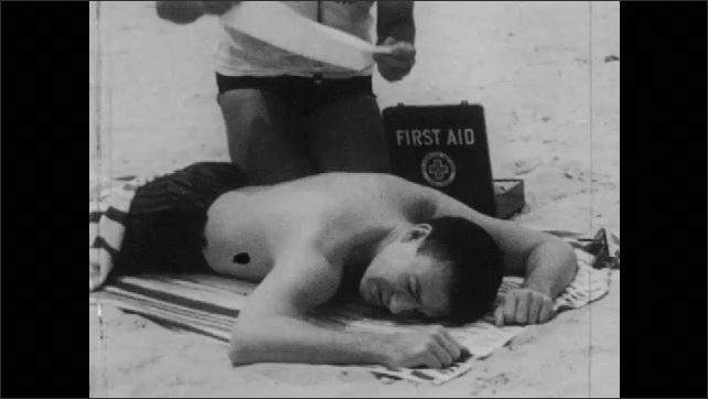 1950s: Bottle of sunburn lotion on beach. Man lays on beach towel, lifeguard applies towel over sunburn blisters.